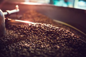 The process of roasting a batch of high quality single origin coffee beans in a large industrial roaster; the toasted beans are in the cooling cycle. Horizontal image with copy space. High contrast with colorful tones.